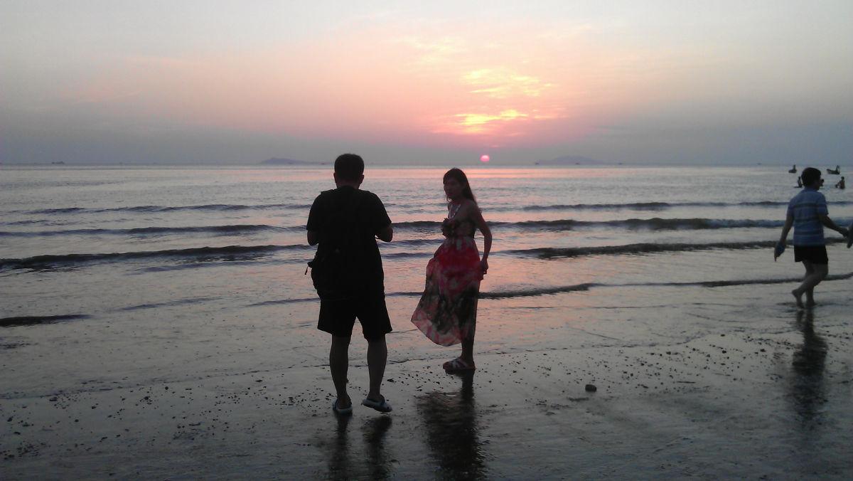 一对小年轻情侣在海边拍太阳落山,我看见他们拍的相片是相当漂亮双手