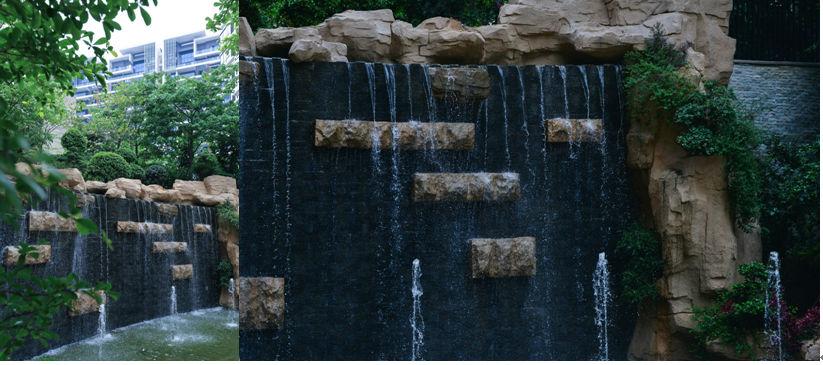 """穿过百米凤凰木大道,""""高山流水""""叠水瀑布映入眼帘,怪石叠水掩映绿意"""
